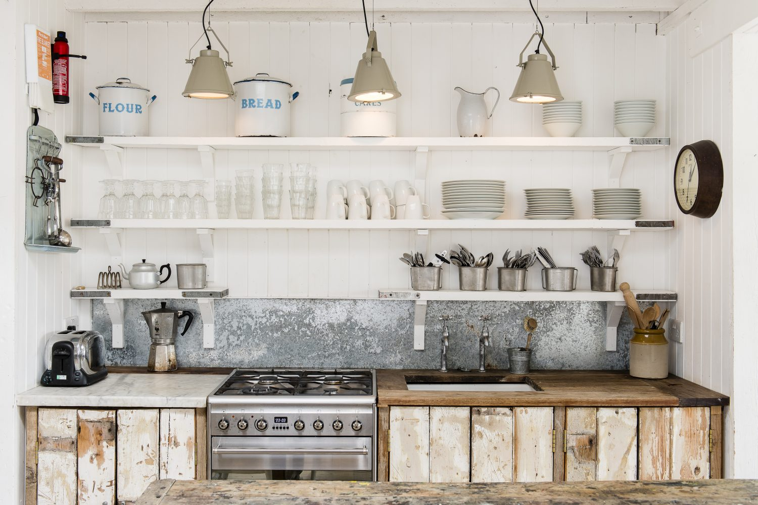 The kitchen is brilliantly simple, with cupboard doors made from boards salvaged from an original ceiling in the house. The white-painted shelves are scaffolding boards. The splashback is galvanised steel and the lights are from Pale & Interesting. The kitchen table provides another preparation area