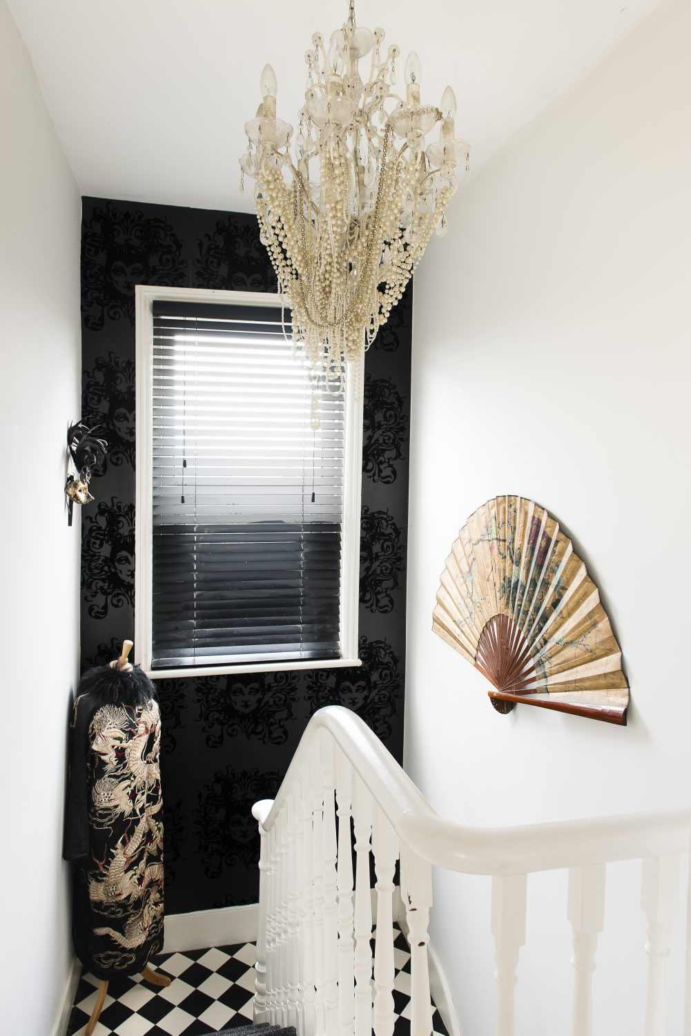 The wallpaper on the half landing was designed by Barbara Hulanicki of Biba fame. Sarah draped the chandelier with strings of pearls Above right: The landing houses her collection of glamorous make up, set off by feathers and black flowers