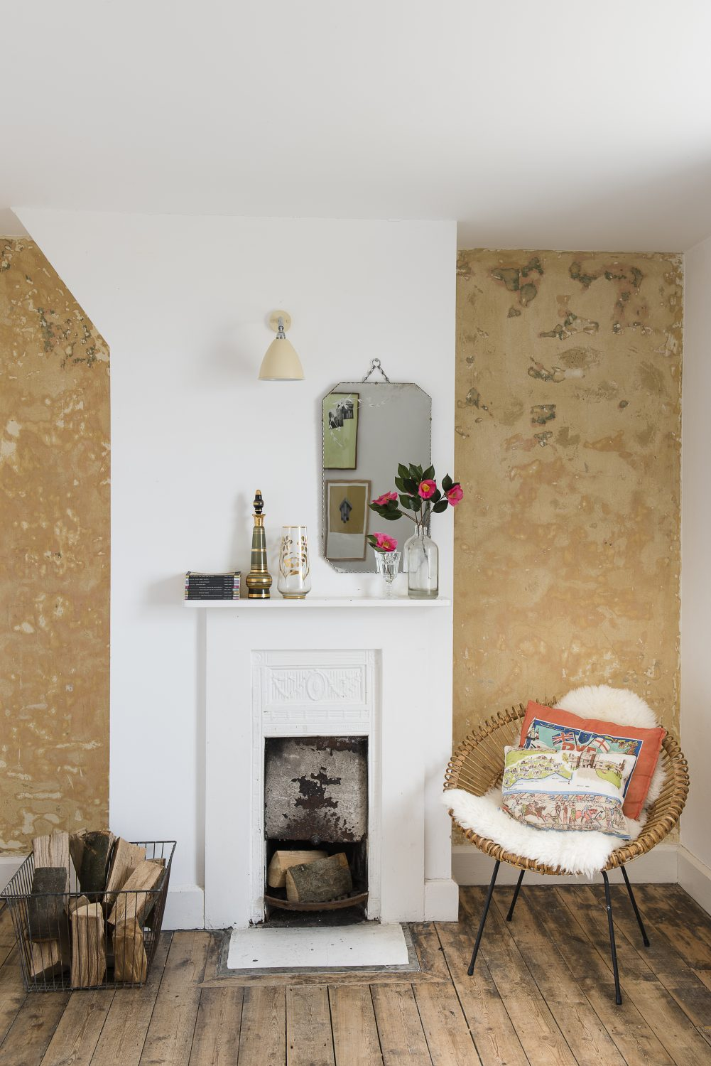 In the East facing double bedroom, Marta stripped off the old wallpaper and liked the distressed plaster beneath it so much she decided to keep it. She has had the 1950s wicker chair for many years. The French painter's ladder was found at Wish Barn Antiques in Rye