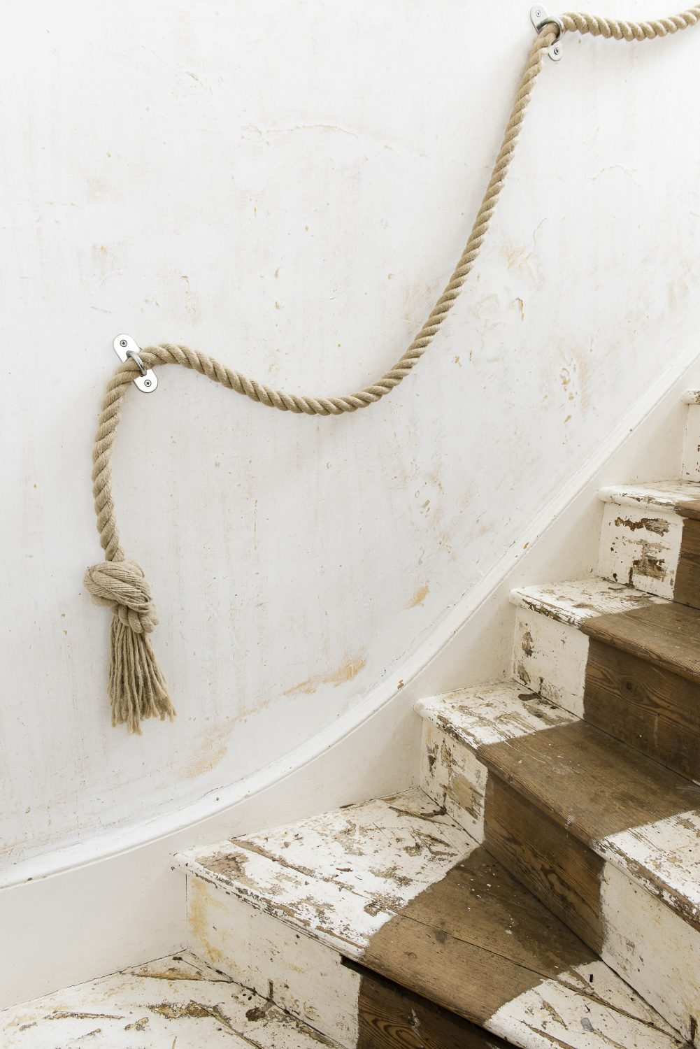 The staircase from the ground floor up to the first floor. The rope handrail is a subtle nod to the maritime connection of the cottage