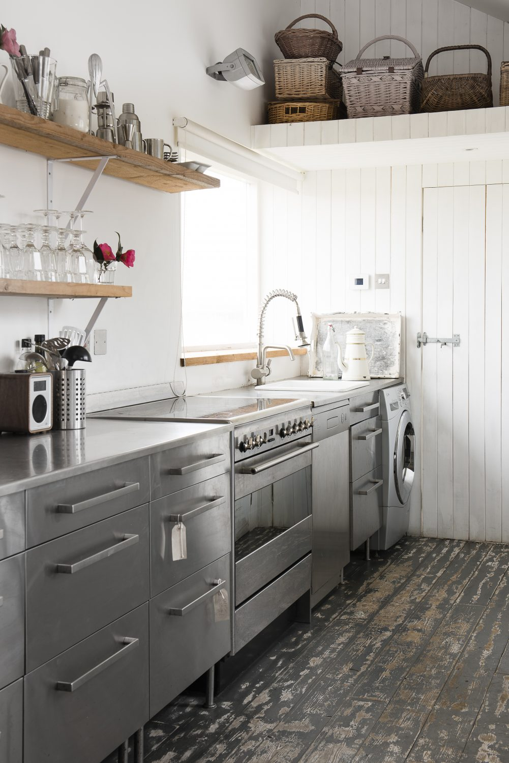 the kitchen has an industrial feel with stainless steel appliances. The drawer unit is from IKEA
