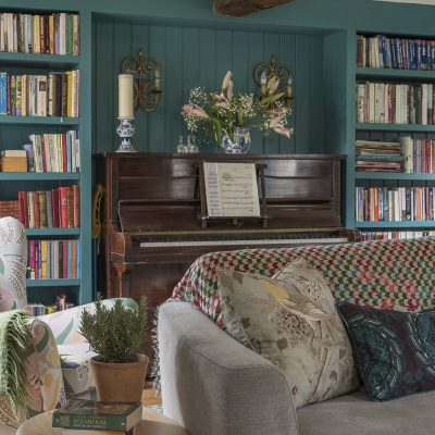 Ally commissioned bespoke bookshelves to create a focal point in the sitting room. The walls are painted in Farrow & Ball's Varta, to add a splash of bold colour.