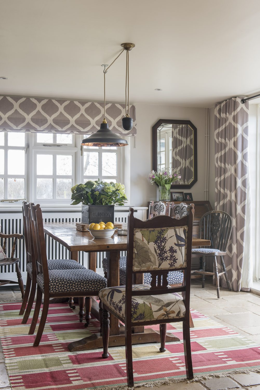The main change Ally made in the dining room, was to turn Jo's table round, so it leads on invitingly from the kitchen. Ally had Jo's existing dining chairs recovered in a mix of prints to contrast the graphic design of the curtains and blinds