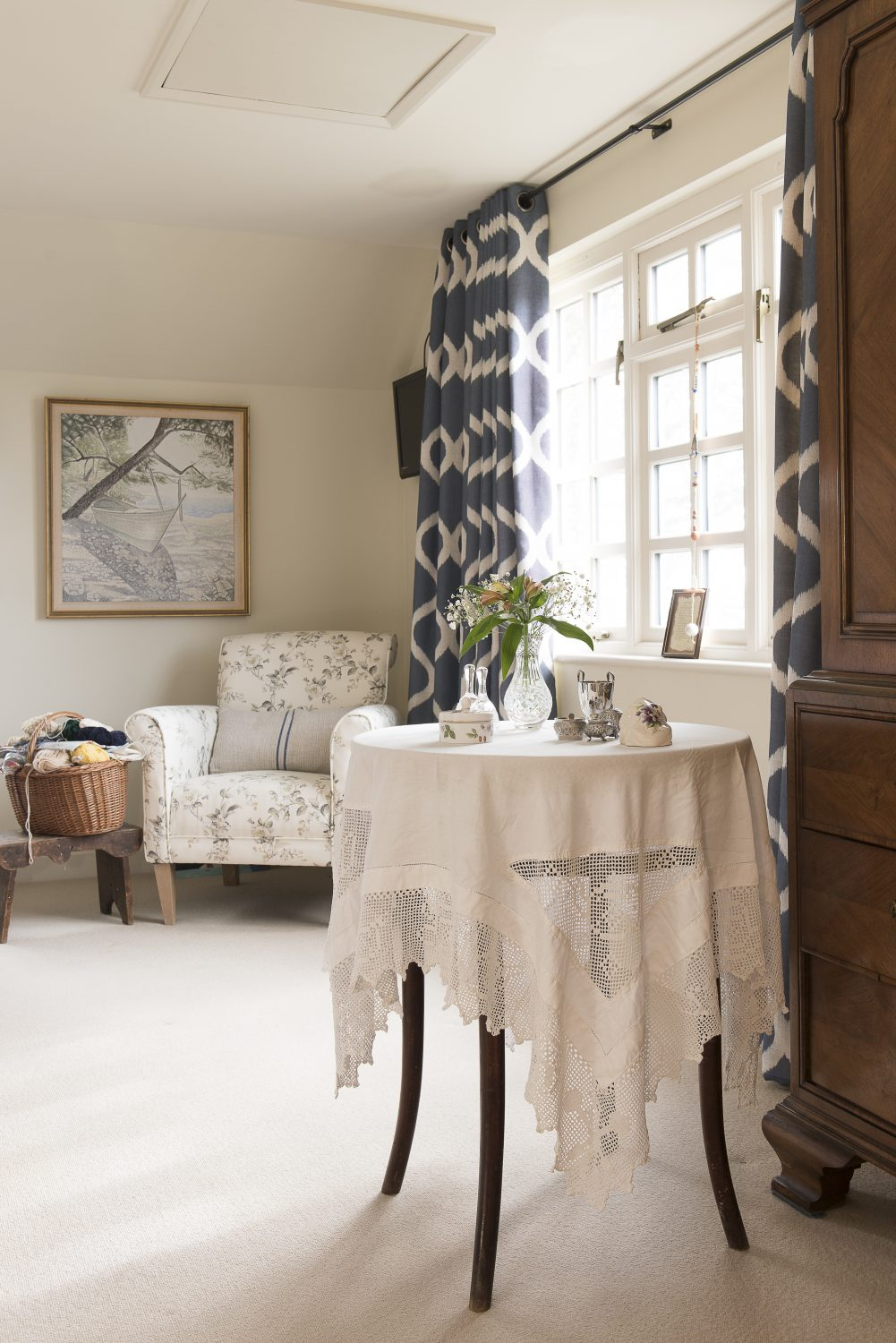 Ally has used the same curtain fabric upstairs in a different colourway. The chair is a Dunelm find, with one of Ally's signature cushions covered in fabric from an old grain sack. Ally urged Jo to buy the beautiful armoire to give the room a focal point.