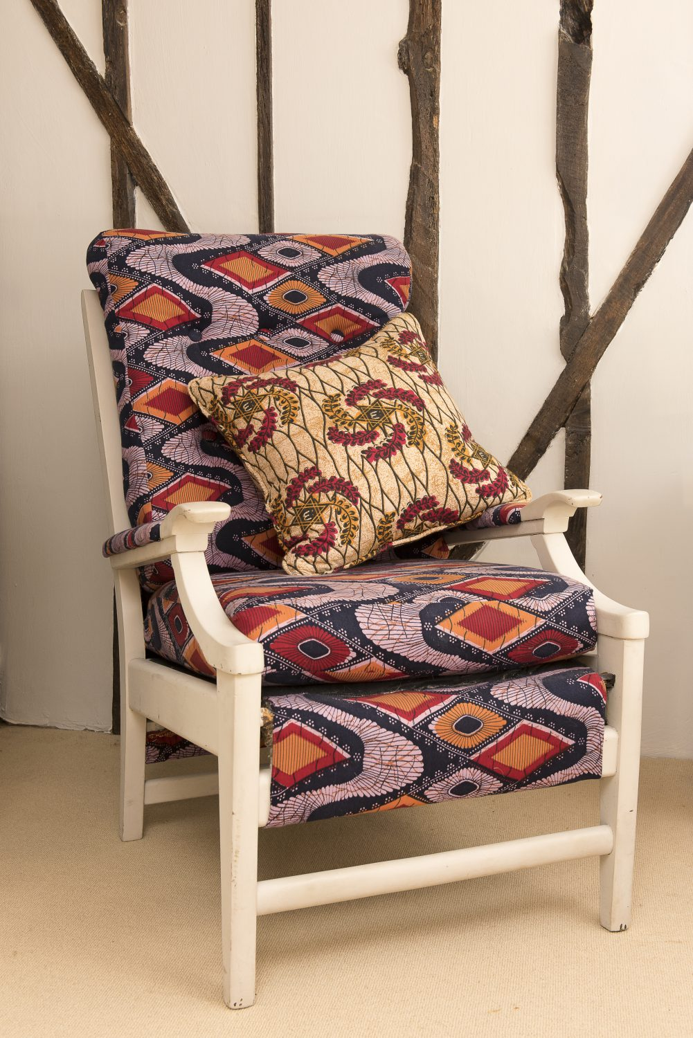 "This chair was a wedding present to Jo's parents. ""It was very comfortable but not very cool,"" she says. ""Ally had it painted white and covered in African fabric – transformed!"""