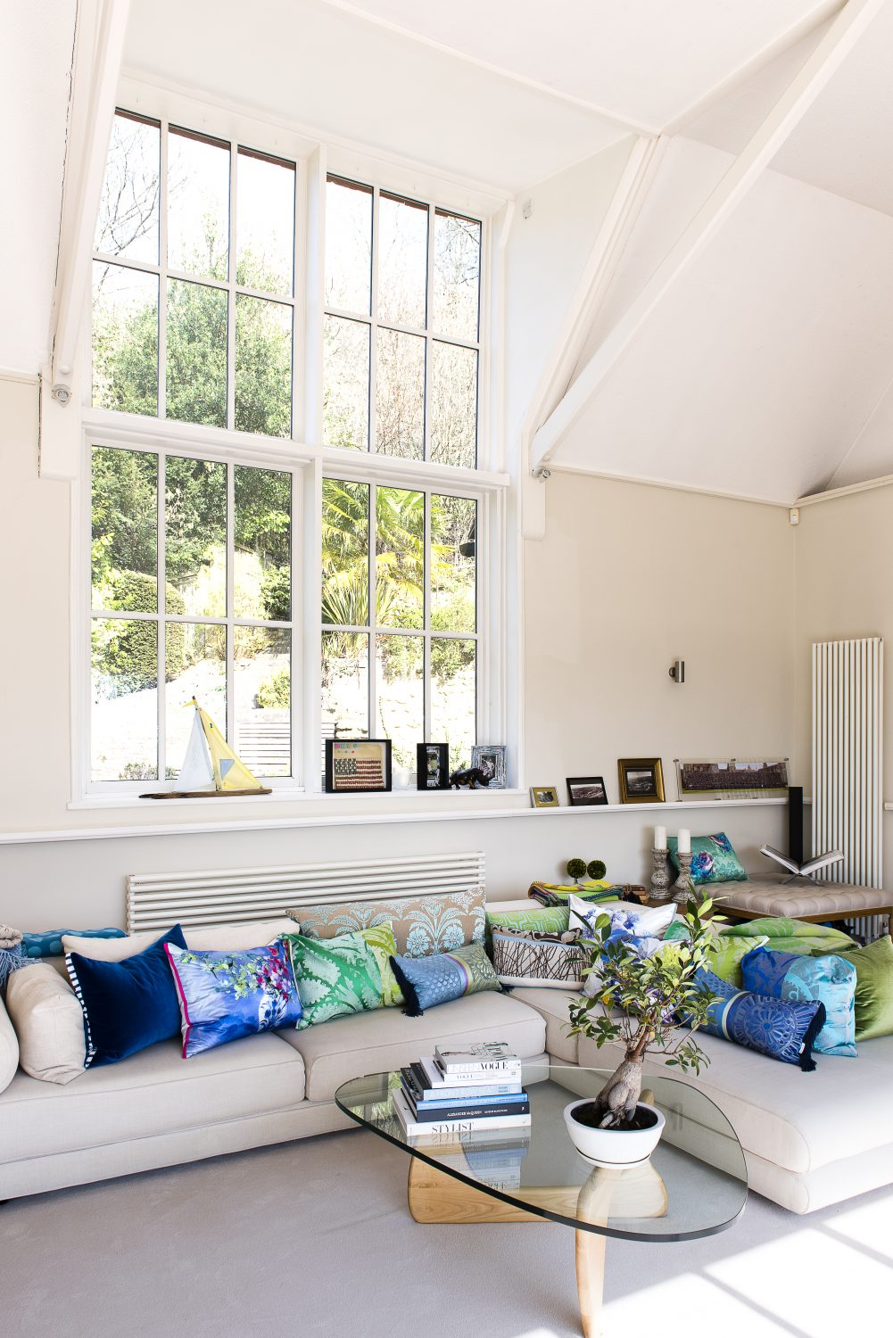 The original north facing window in what was the studio of the Victorian artist who originally owned the house. All the cushions on the Roche Bobois sofa are covered in Designers Guild fabrics. The Noguchi coffee table is from Heals