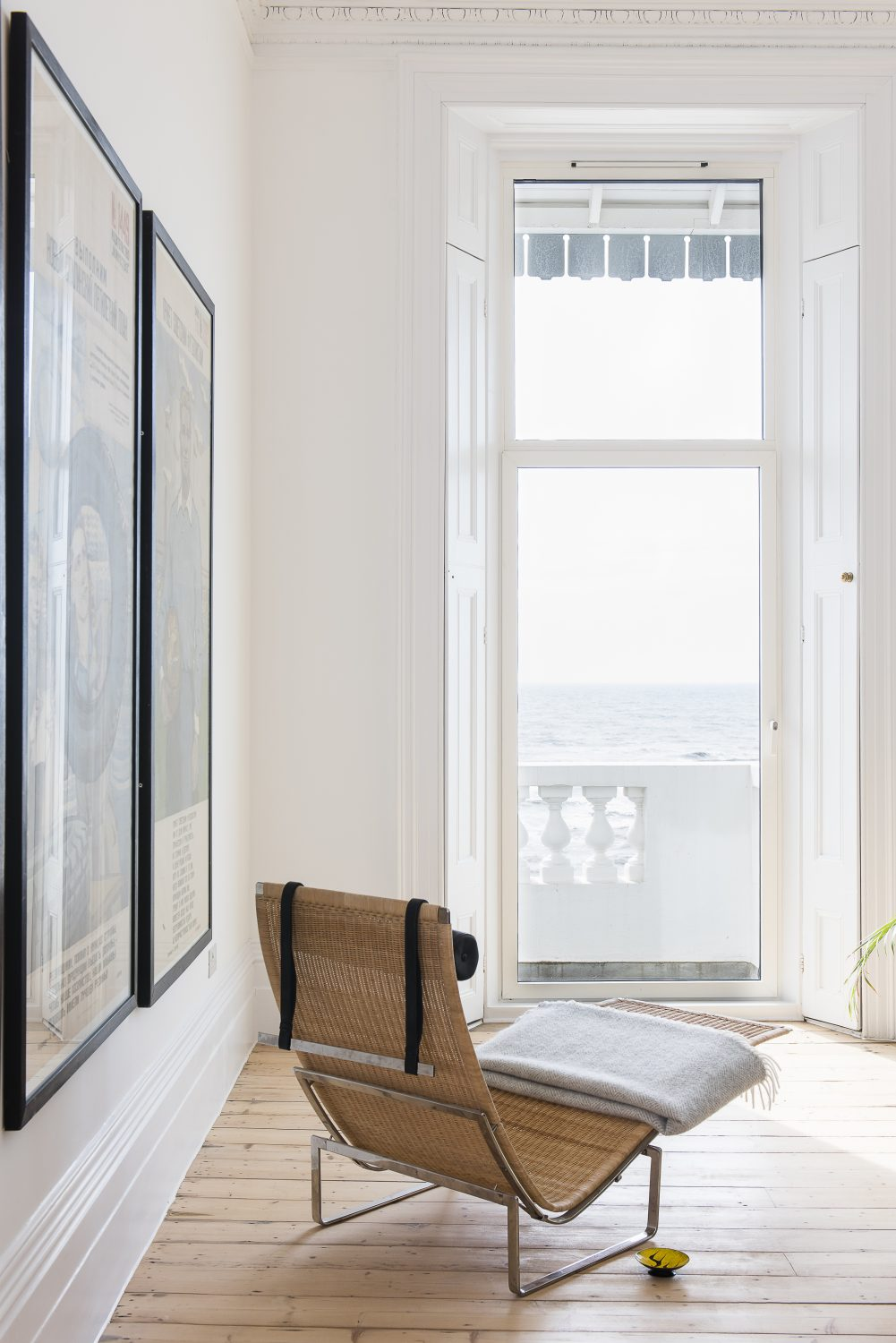 The main living area has floor-length windows with views out to sea. The rattan chaise longue is by Poul Kjaerholm