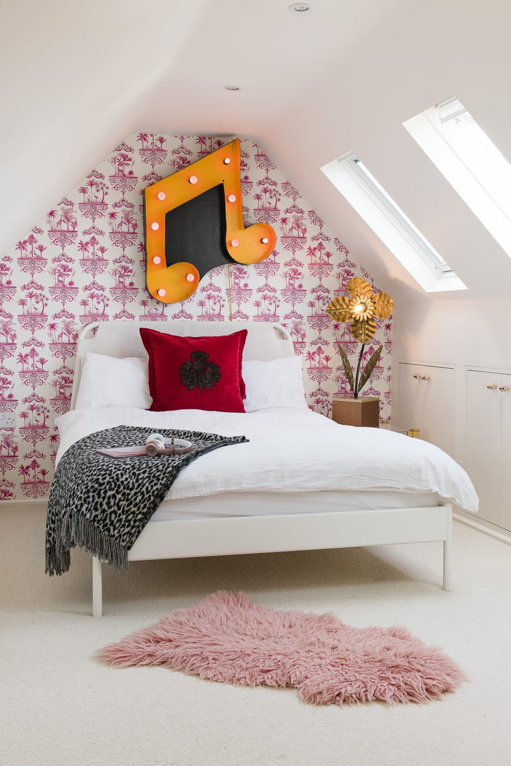 Daughter Madeline's bedroom. A metal music light with yellow and pink bulbs hangs above the bed