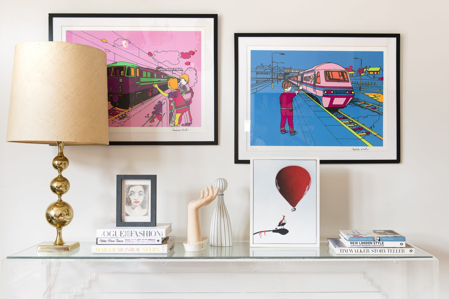 A row of prints by Ben Eine line the wall above a 1930s Perspex console table
