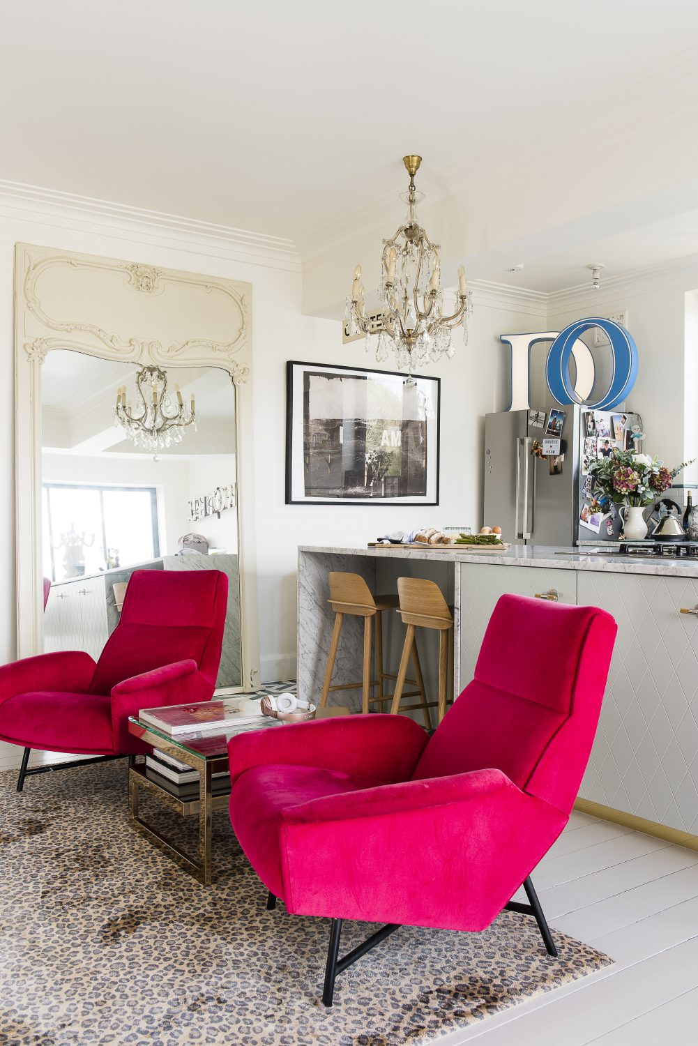 Two hot pink velvet vintage armchairs create a cosy kitchen seating area Above right: A Vivienne Westwood for the Rug Company tapestry bought with Samantha's inheritance from her grandparents