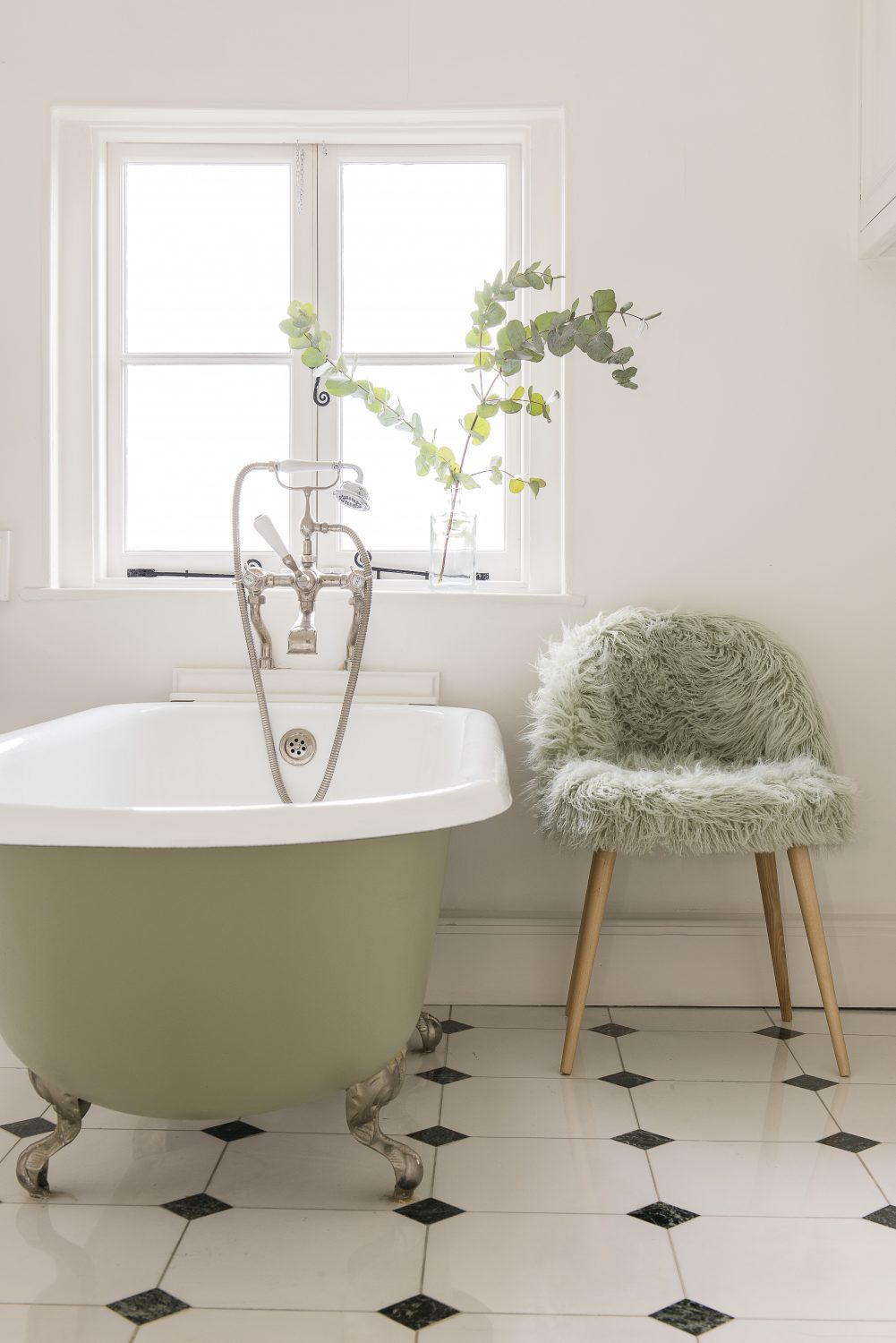 The adjoining bathroom continues a light and fun attitude with a green bathtub