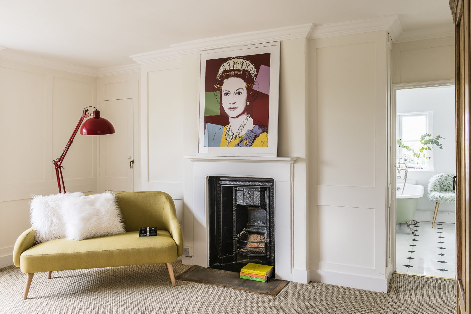 The top floor's main bedroom is fun and colourful with a portrait of the Queen, a yellow sofa and huge red Anglepoise lamp