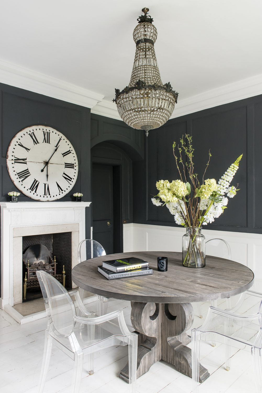 In the dining room Philippe Starck Ghost chairs set off the black walls. The clock on the mantelpiece is an antique station clock from a London market. The chandelier is from a vintage shop in Notting Hill