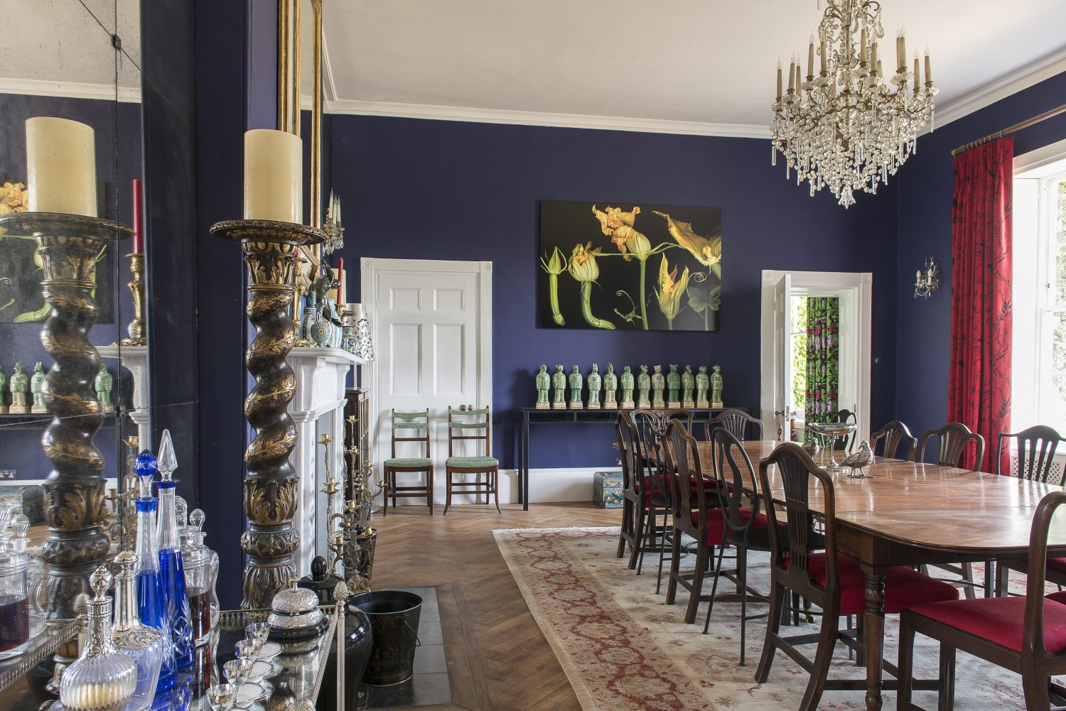 The dining room is painted in Thai Sapphire by Little Greene. The cast iron dining chairs are from Oka. The botanical photograph is by Isabel Bannerman
