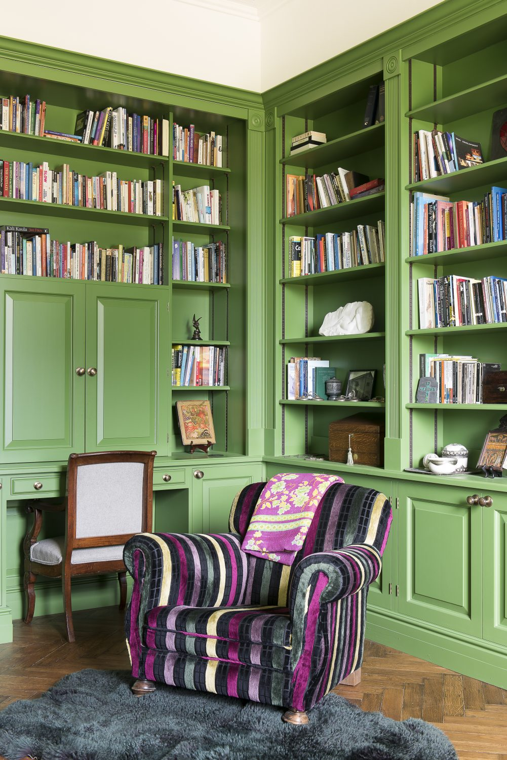 The wonderful pea green paint in John's study also by Little Greene. The curtain fabric is by Lacroix. John's computer is cleverly hidden behind doors in the bookshelves. The Chinese porcelain Foo Dogs – or 'guardian lions' – on the mantelpiece are another of Jane's favourite things to collect