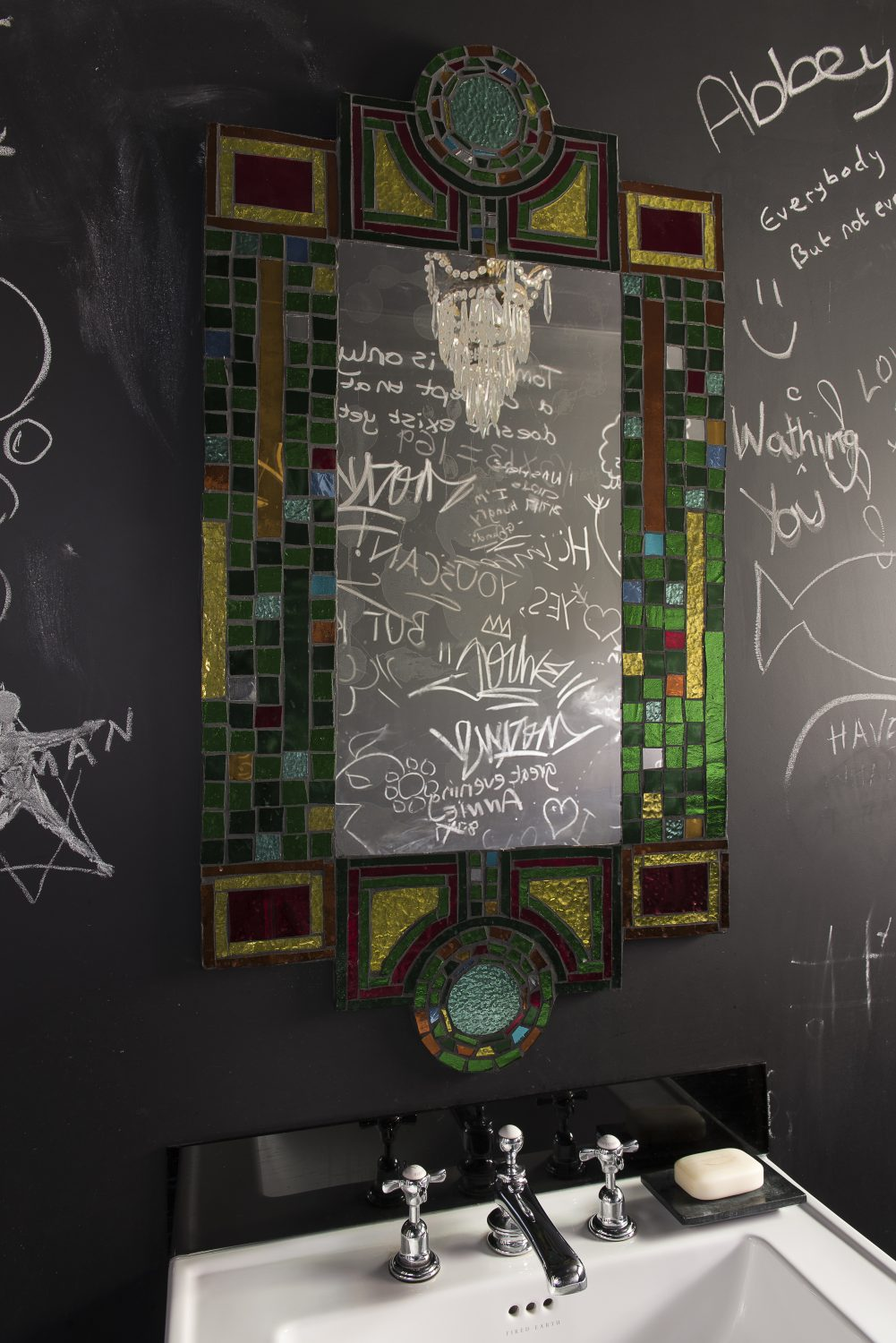 The walls in the 'blackboard loo' have been enthusiastically graffitied by the whole family Above: The loo window is filled with coloured Duralex tumblers, reflected in the mirror on the window sill