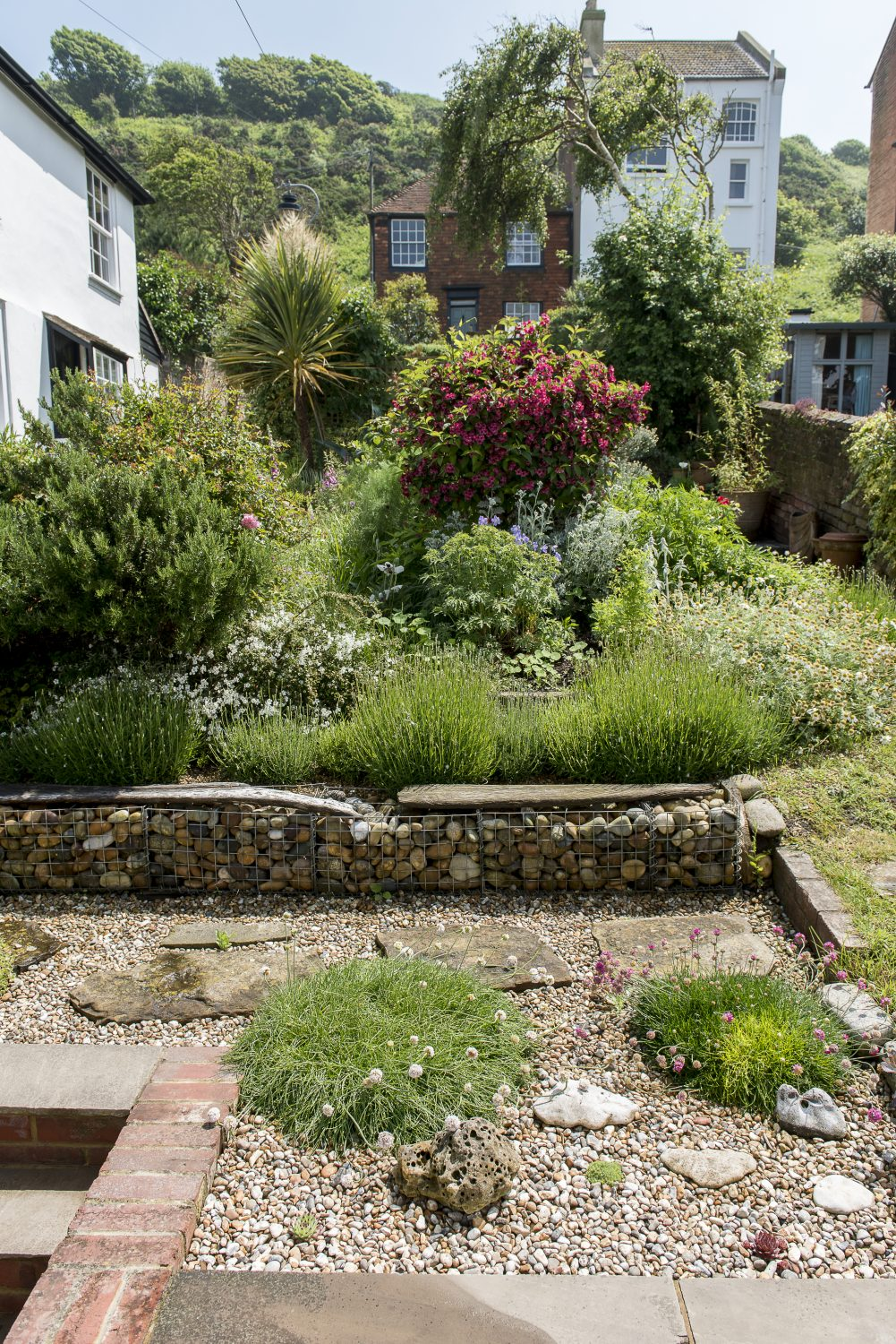 The terraced garden at the front of the house. The previous owner had created the garden from scratch and Melanie has enhanced and edited it, adding her own touches, including a seating area made out of metal gabion baskets filled with pebbles