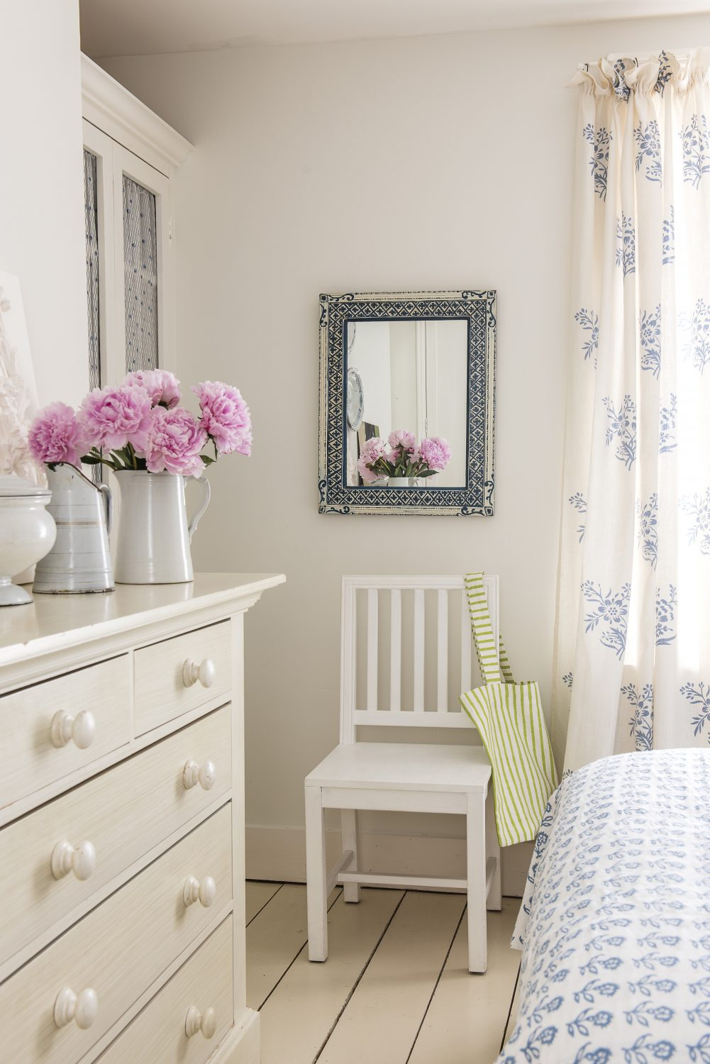 The bedroom combines white-painted furniture and floorboards with blue and white Room 100 fabrics