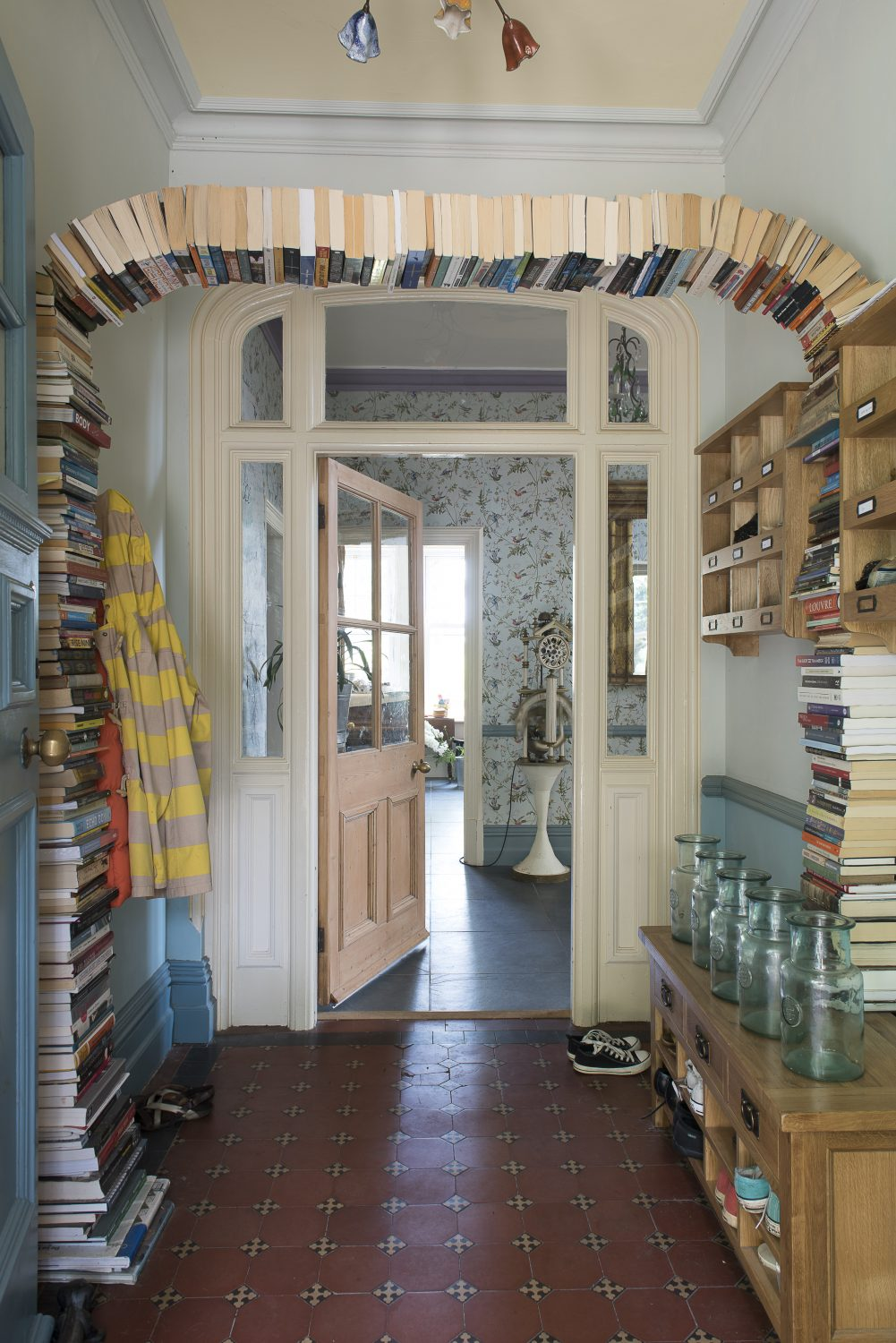 An arch of suspended books wittily frames the entrance to Archer Lodge