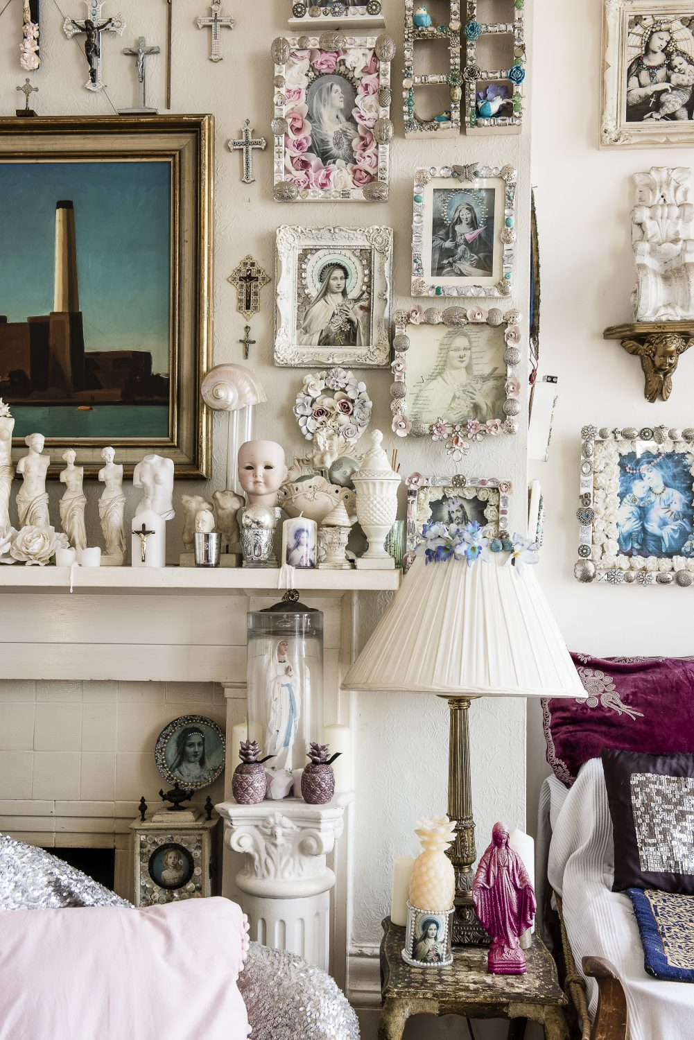 An ornate French mirror is surrounded by some of Sassy's artistic creations – pieces of religious iconography with playful twists of flowers, shells, crystals and lights, all in her signature pale colour scheme of white, pink and blue