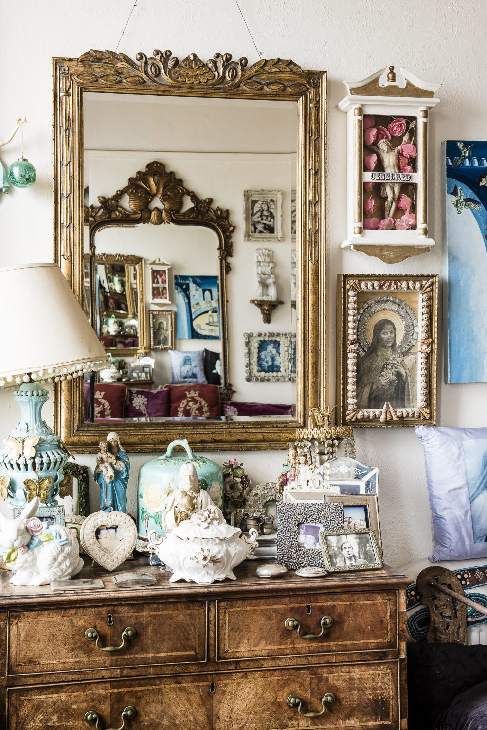 An antique chest of drawers holds a series of family heirlooms and photographs