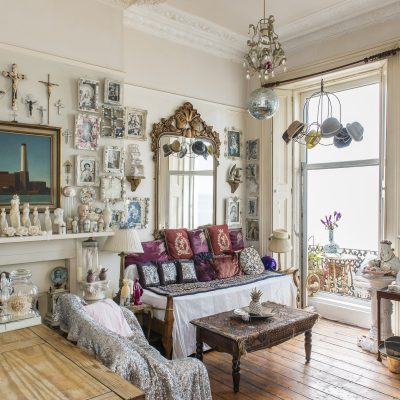 Dominating the area by the window is a large sofa/day bed covered with pastel throws and richly ornate deep red and gold velvet cushions