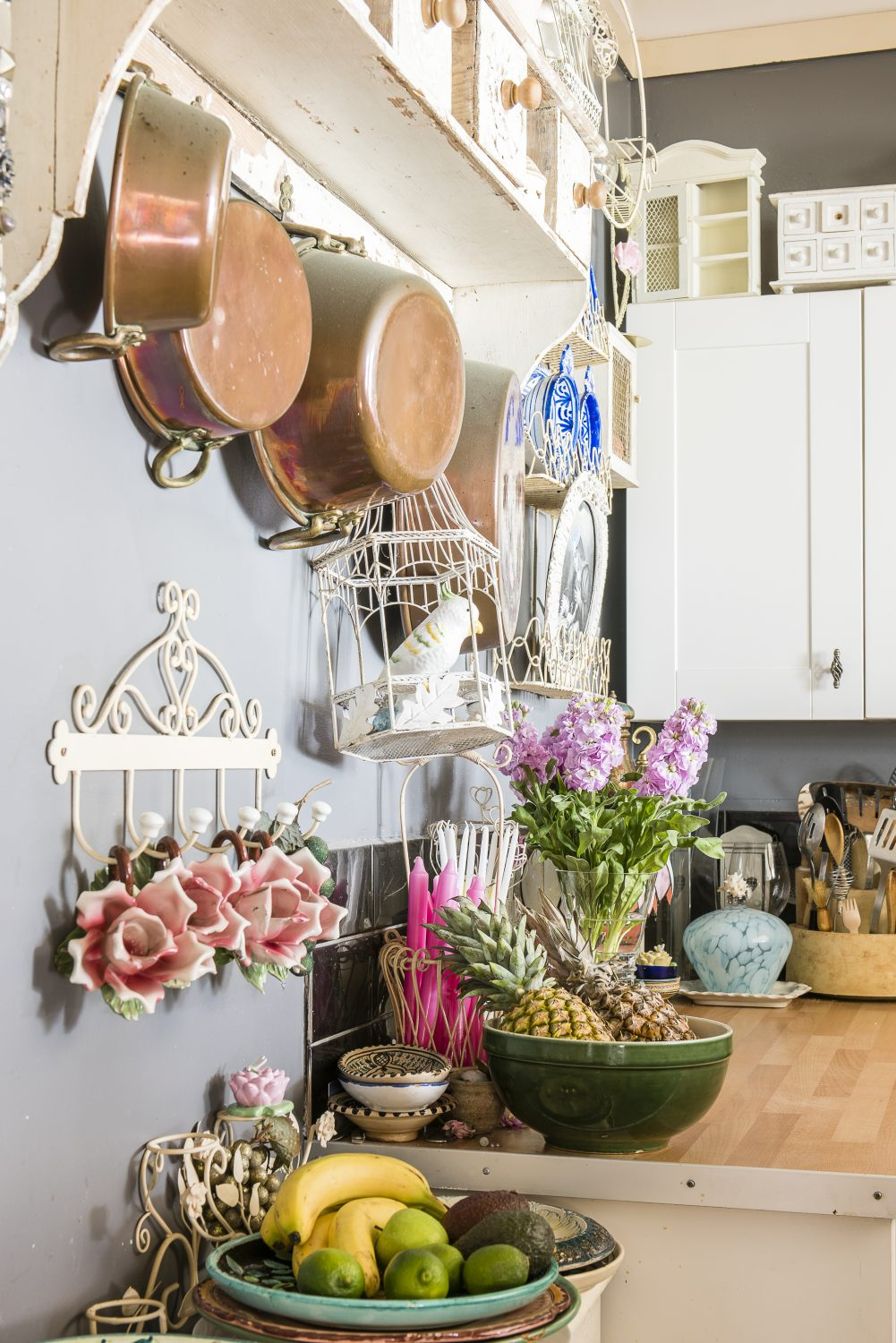 The kitchen sings with Spanish pottery, hanging vintage copper pots and occasional touches of whimsy in the form of a birdcage and ceramic roses