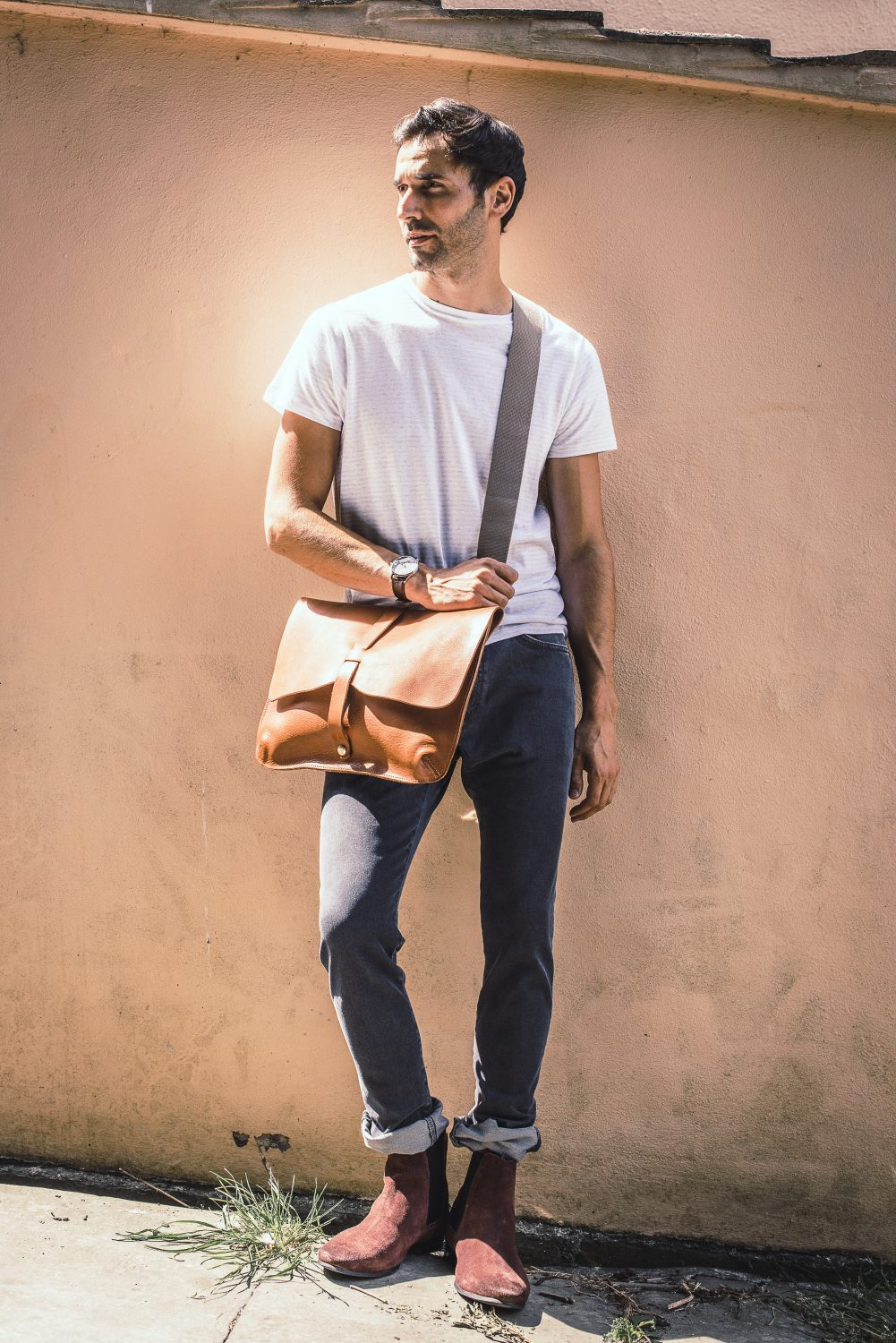 A messenger bag sharpens the most casual combo of T shirt and jeans