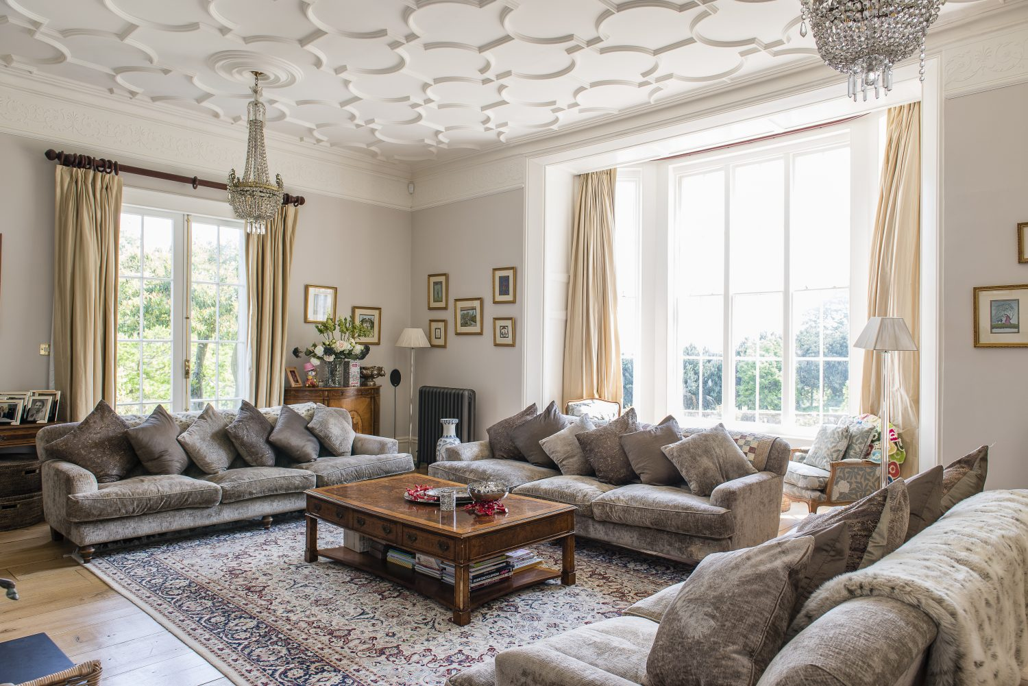 Ornate heirloom chandeliers draw the eye to the ceilings in the sitting room