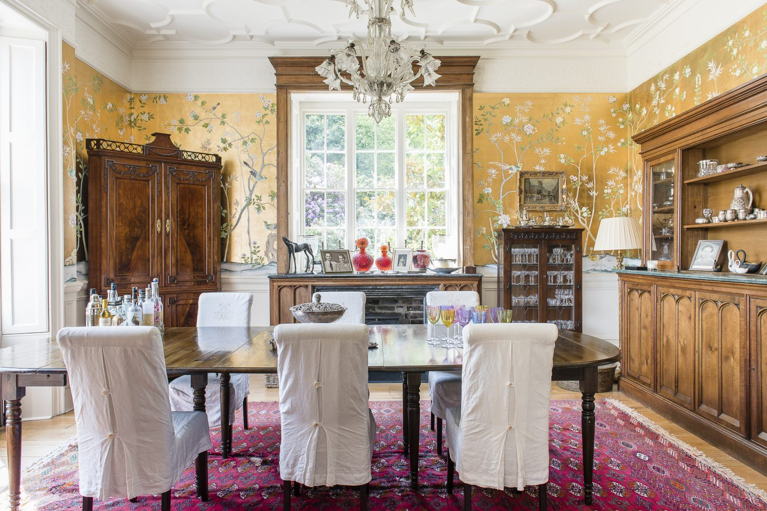 The dining room was once a snooker room for RAF officers billeted in the house during World War II. The wallpaper is by De Gournay. The coloured vases are from Venice, a special place for Chris and Lillie, which inspired one of the Lavender & Lillie fragrances