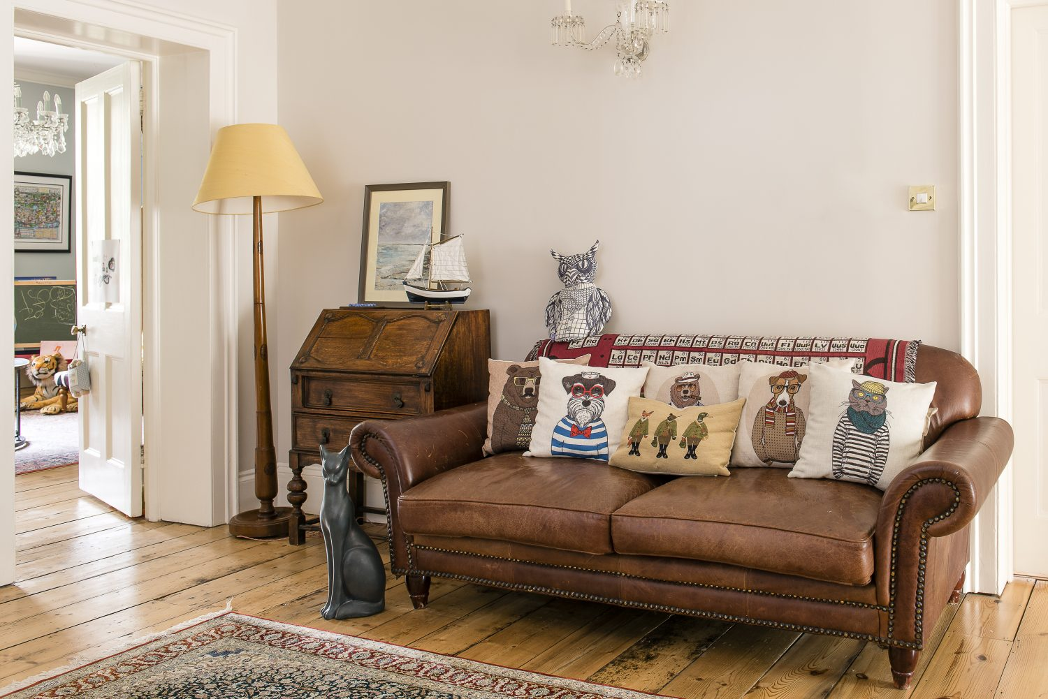 A sofa on the landing. The original floorboards were sanded and restored. The animal cushions are by Sass & Belle