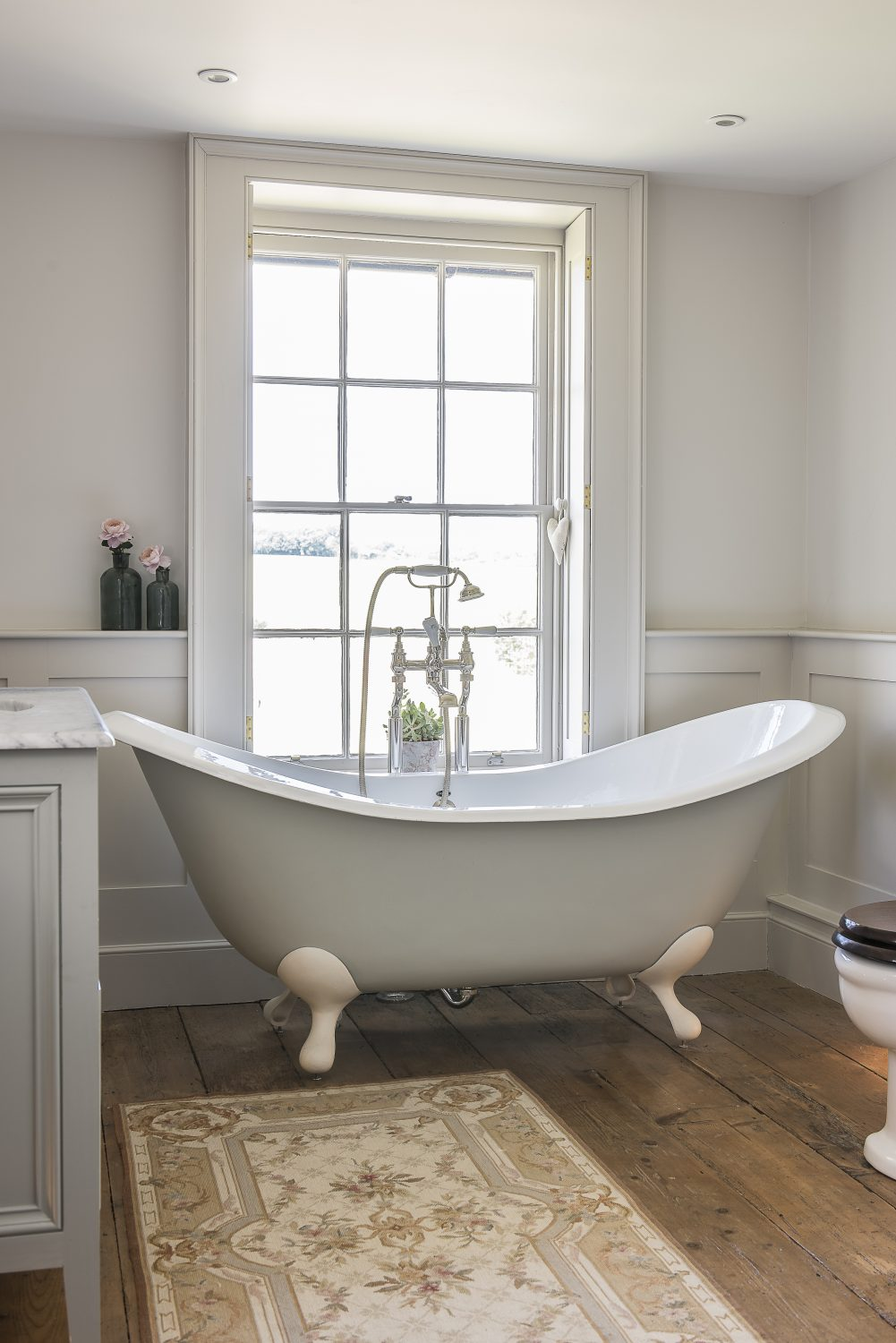 The slipper bath, from Tenterden Bathroom Shop, has views through the sash window over the horse paddocks. Wooden panelling was added on lower walls to give a classical feel.