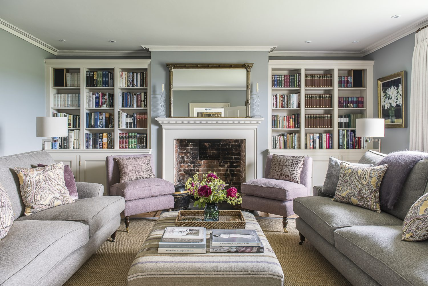 More bookshelves in the drawing room. The oversized ottoman is upholstered in a William Yerwood jute stripe. The patterned cushions are a Nina Campbell linen. The brass lamp is by Porto Romana. The painting client's own