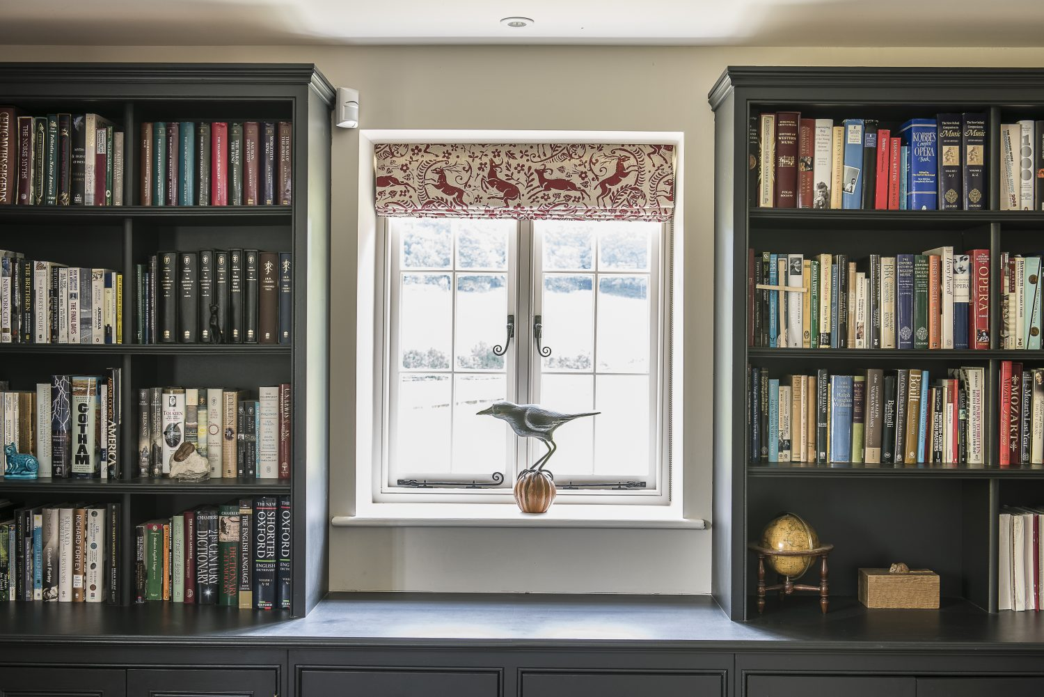 The book-lined study leads into the kitchen. The blind fabric was designed by Lindsay Alker
