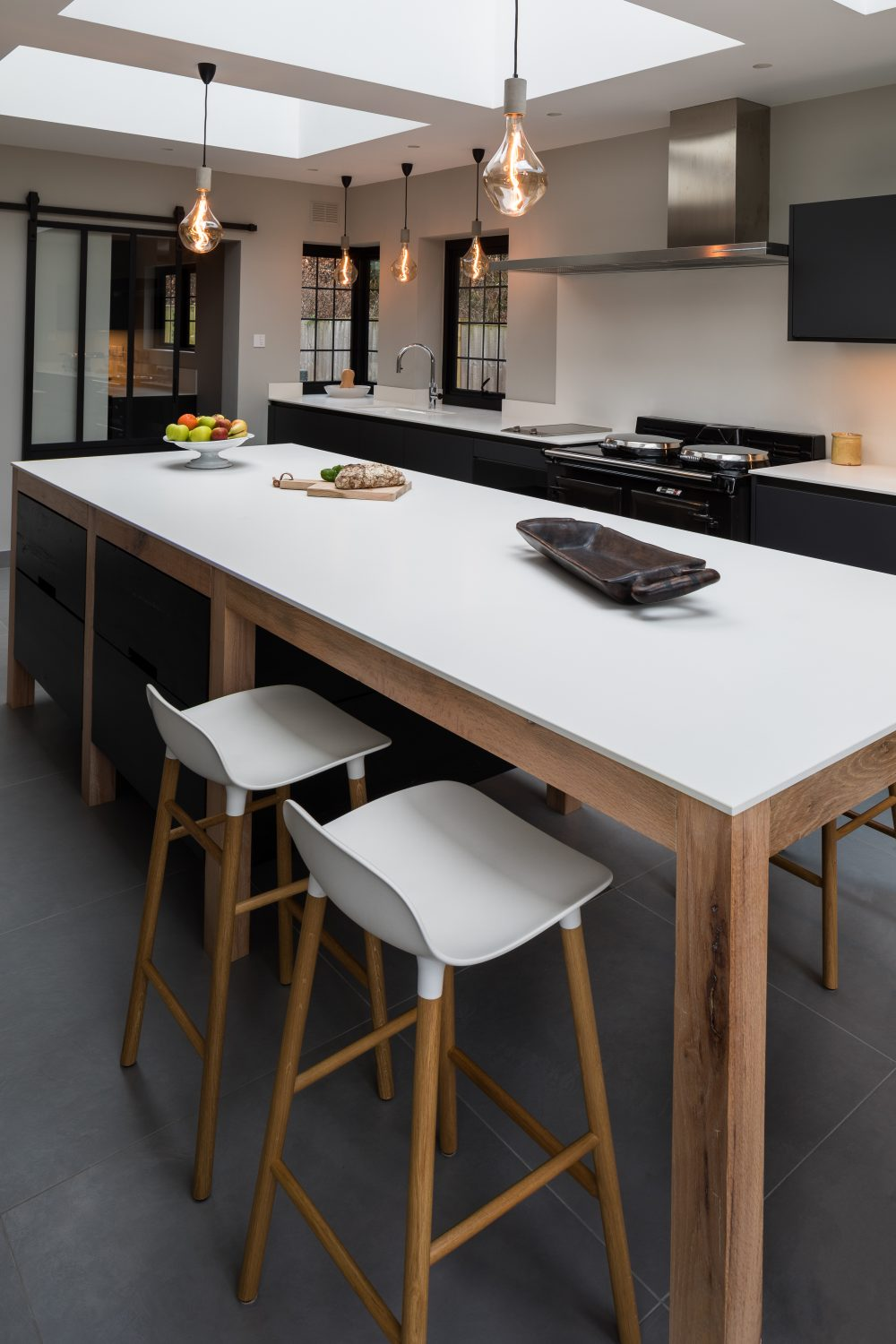 Adaptations The island is bespoke in American reclaimed oak with ebony-stained drawer fronts, the cabinets are from the handleless extreme matt range in Carbon. Kitchens from £25,000 01932 584940 adaptations.uk.com