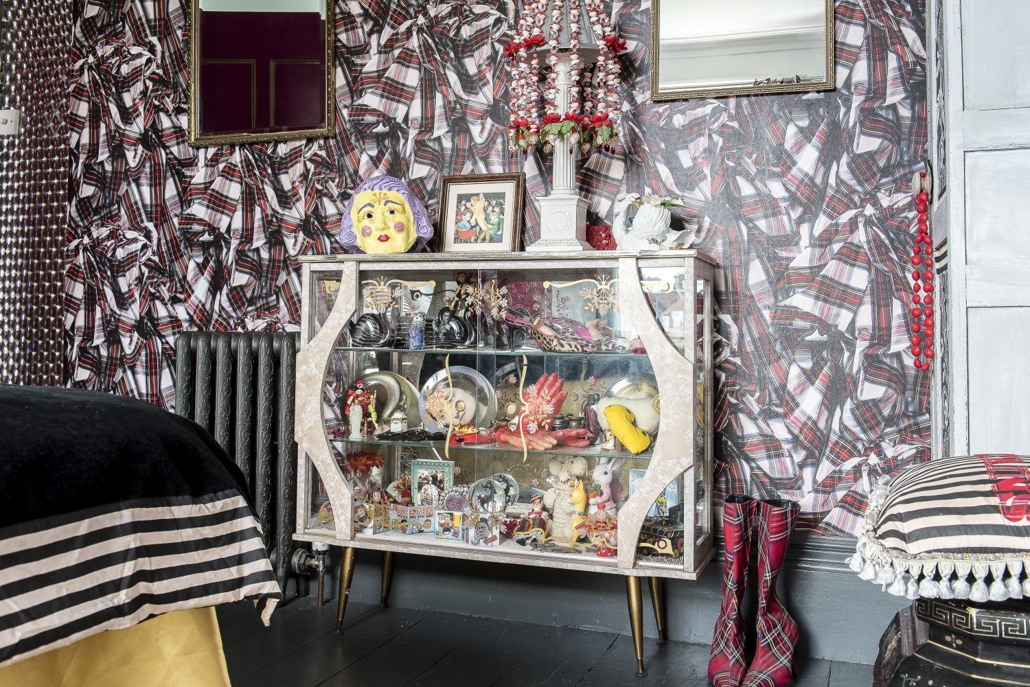 The 1950s cabinet contains mementoes from Annemarie's life. The tartan wallpaper is by Vivienne Westwood