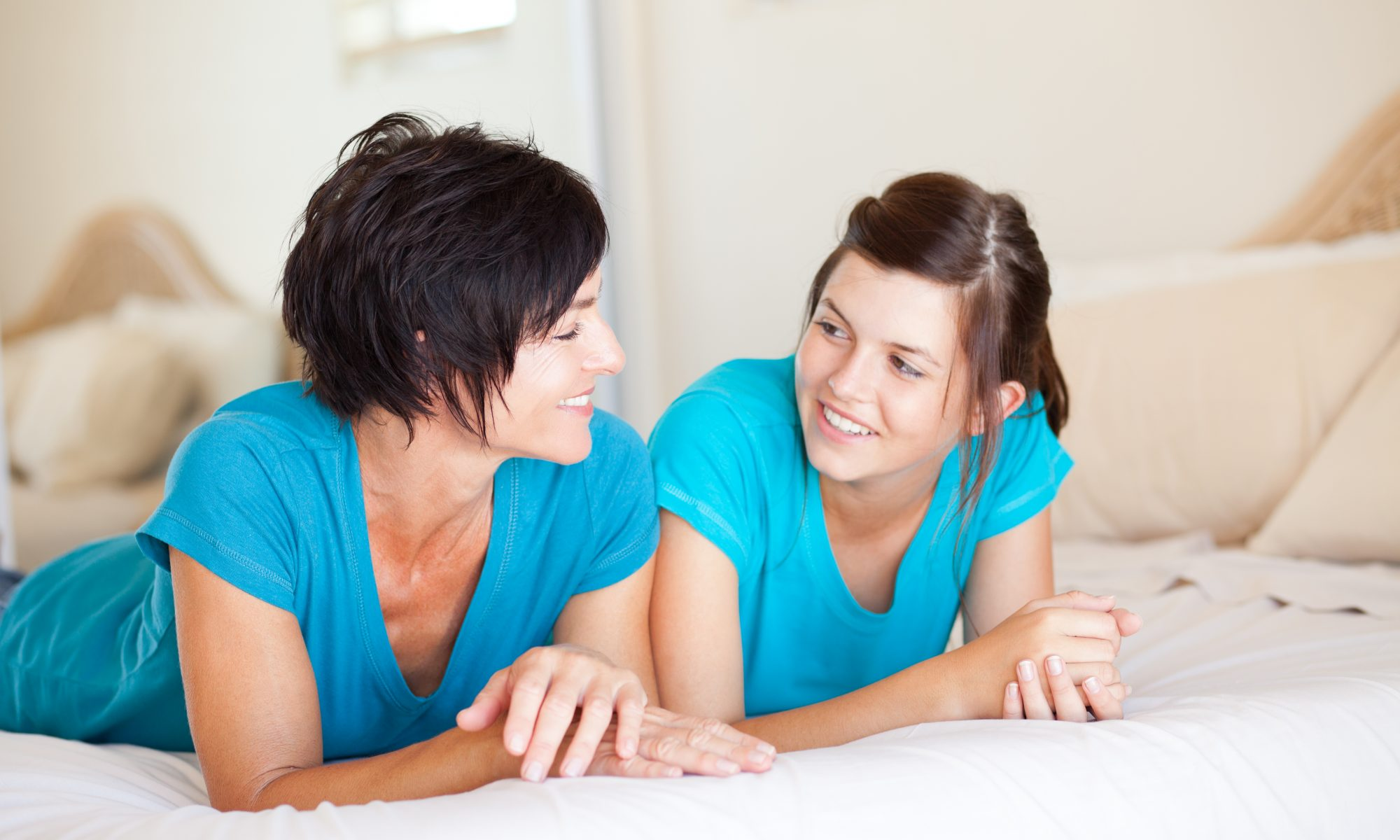 middle aged mother and teen daughter chatting on bed