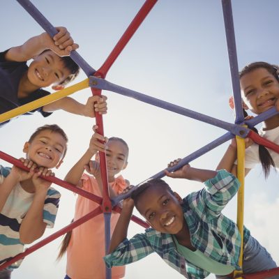 Portrait of happy schoolkids looking through dome climber at school playground