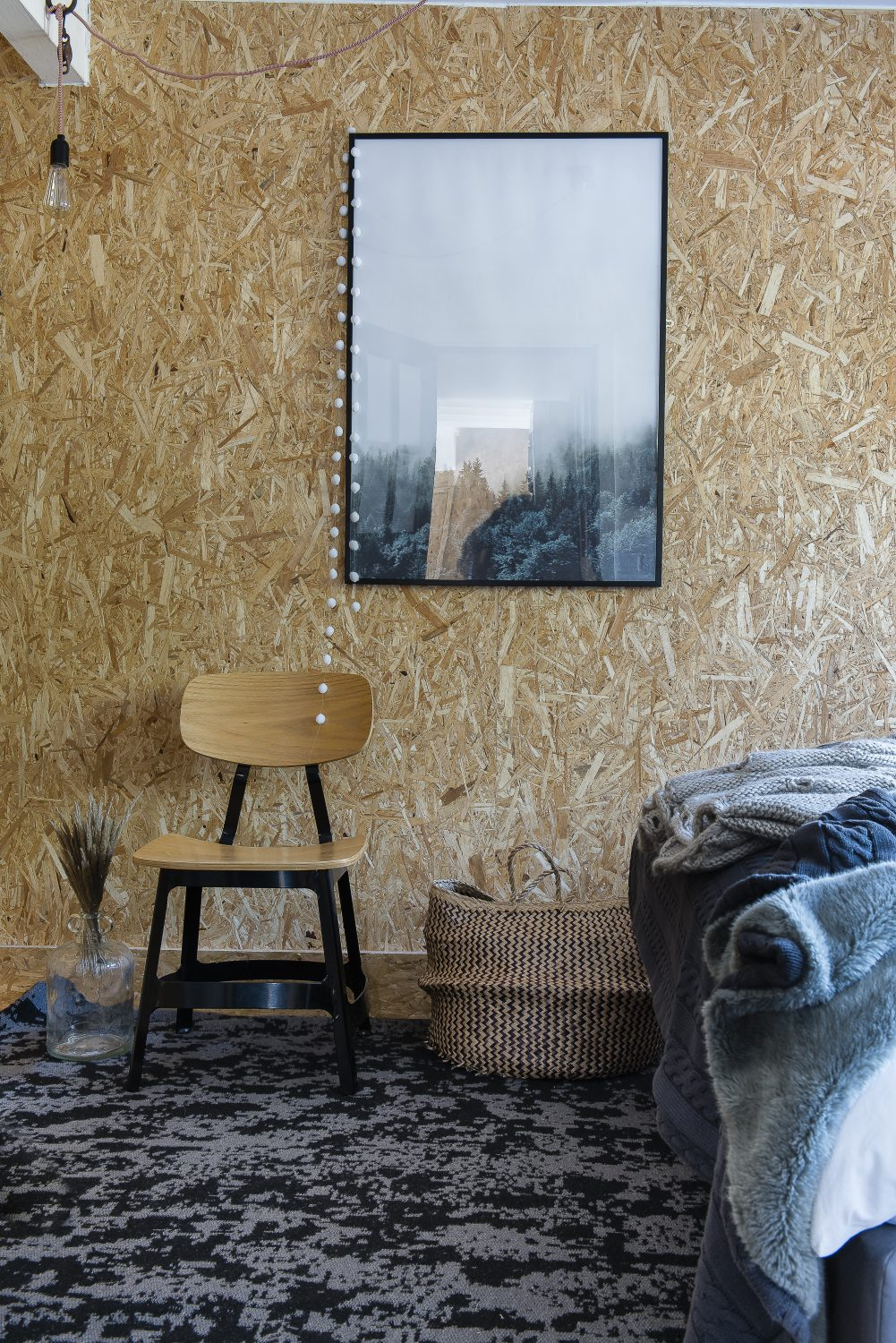 A wall of OSB (a form of chipboard) in the bedroom creates a decorative effect with a utilitarian material