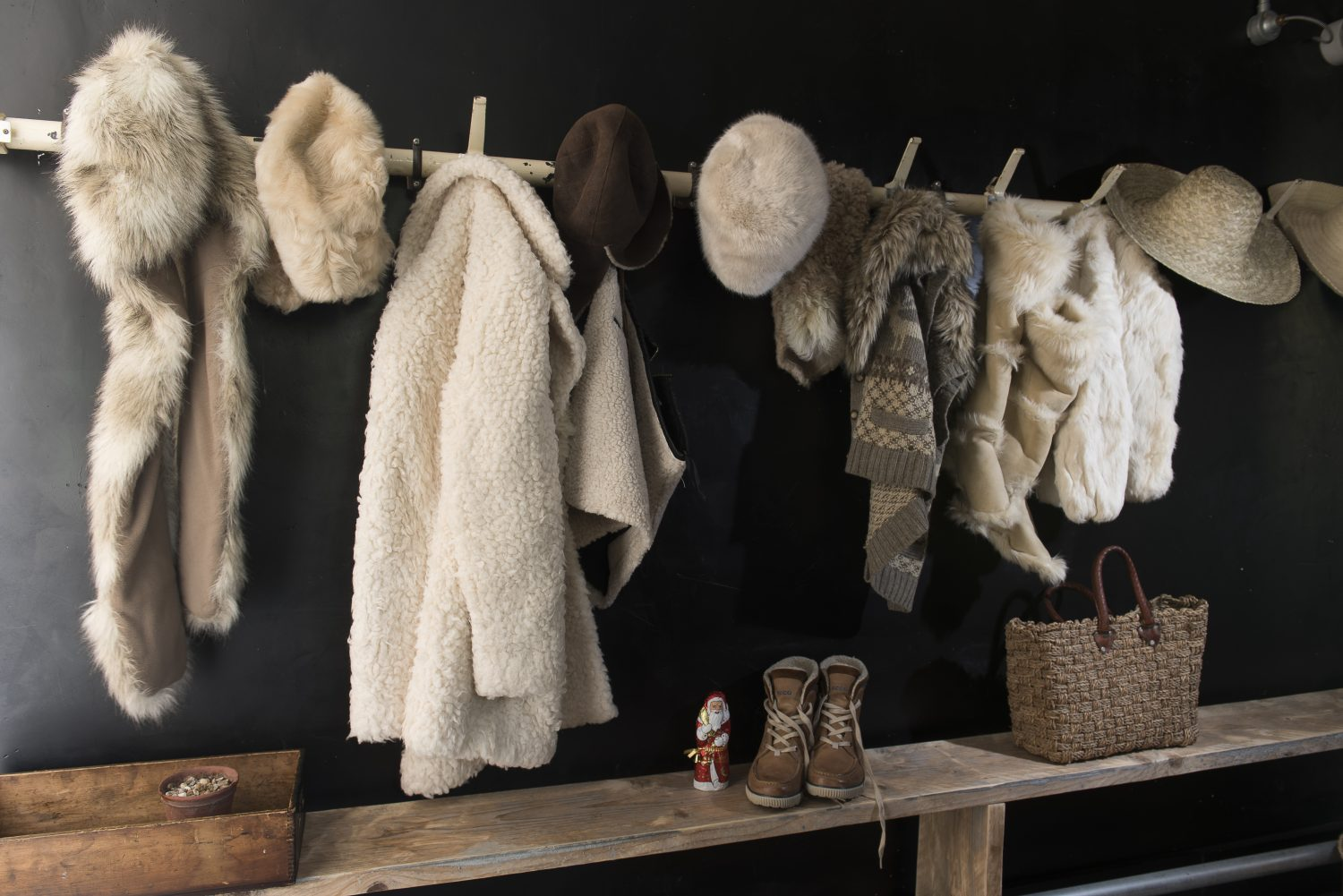 A row of pegs from an old school changing room, bought in Rye, is cosy for winter with an array of shearling and fake fur coats – in summer it's home to beach towels and sun hats