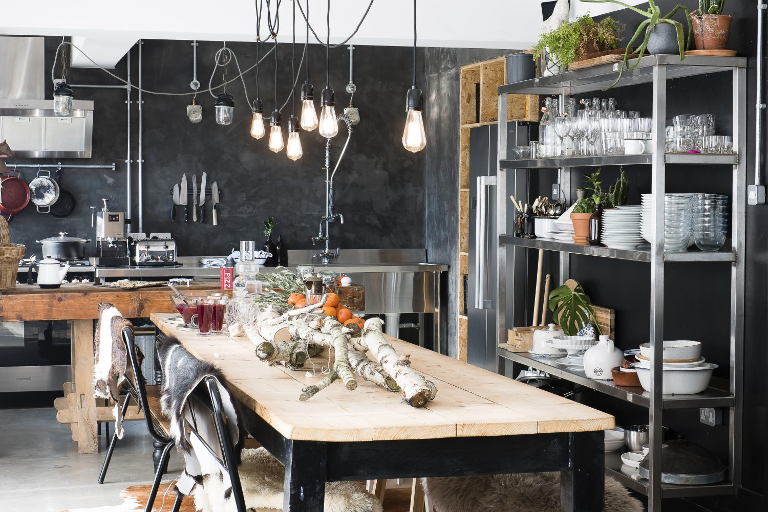 Matt made the kitchen table with old scaffolding planks, so it would be big enough to seat 14 people. The kitchen island behind is an old carpentry table given to them by the previous owner of the house – after they had been looking for one for ages 'a magical gift'