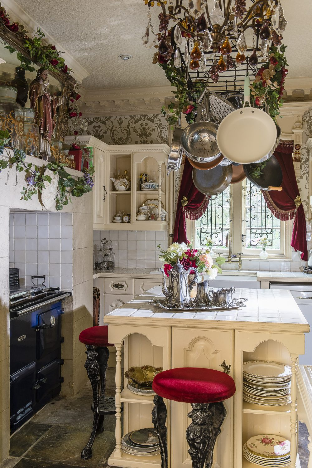 The bespoke kitchen has a central island where Kim displays her charity shop and boot fair mix and match plates