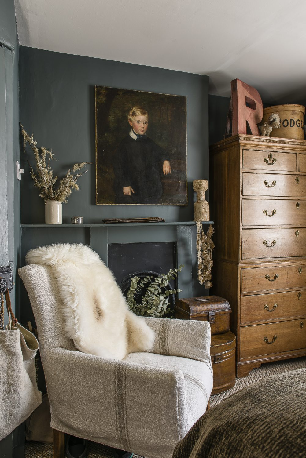 This chair, in the master bedroom is covered with a loose cover made from old grain sacks. The portrait of a boy and the double height chest of drawers were antique finds