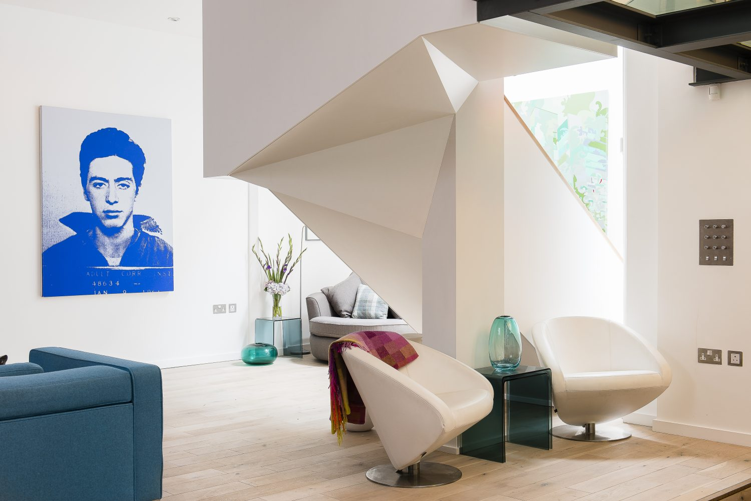 Chairs by Arketipo and white urns from The Conran Shop complement the geometric shapes of the staircase. The mug shot of Al Pacino is from the Pig Portrait series by Russell Young