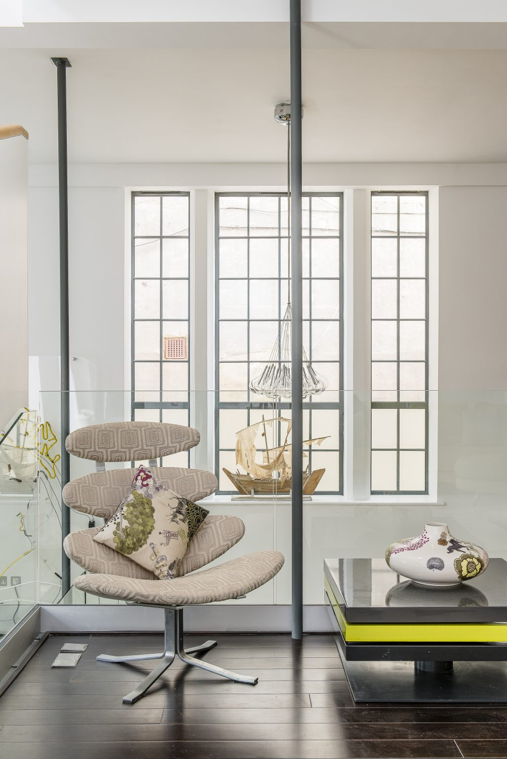 On the mezzanine balcony, the Perspex table is by Ligne Roset and Ian bought the model boat from The Conran Shop