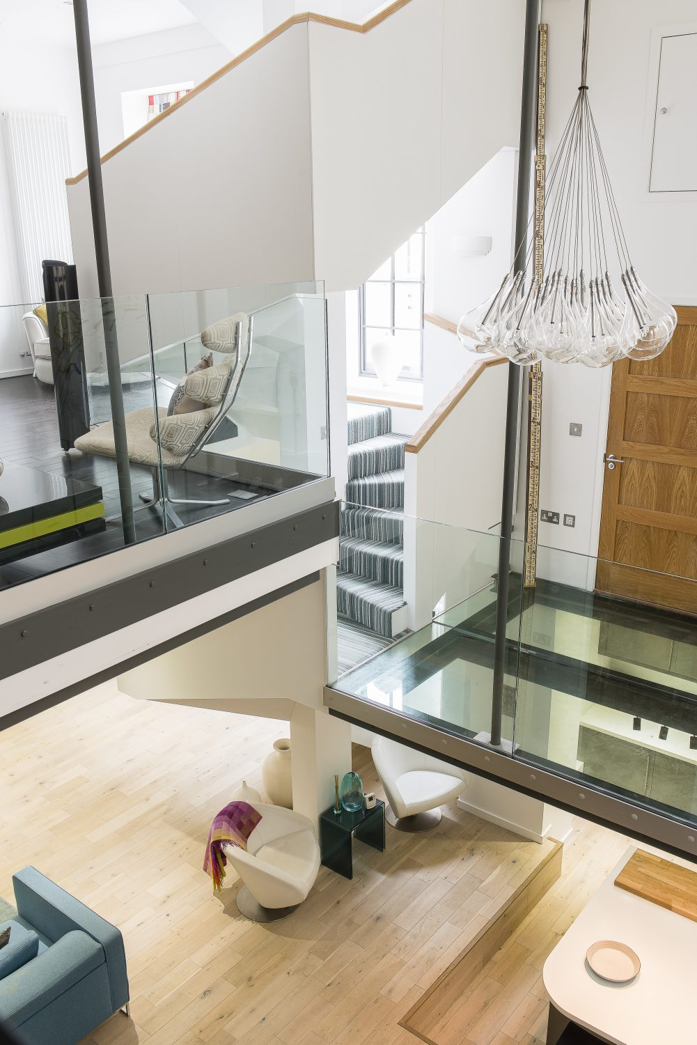 Three levels were created in the huge space, linked by a bespoke staircase. The light is by Christian Cubina. It took 12 men to lift the glass floor of the mezzanine into place