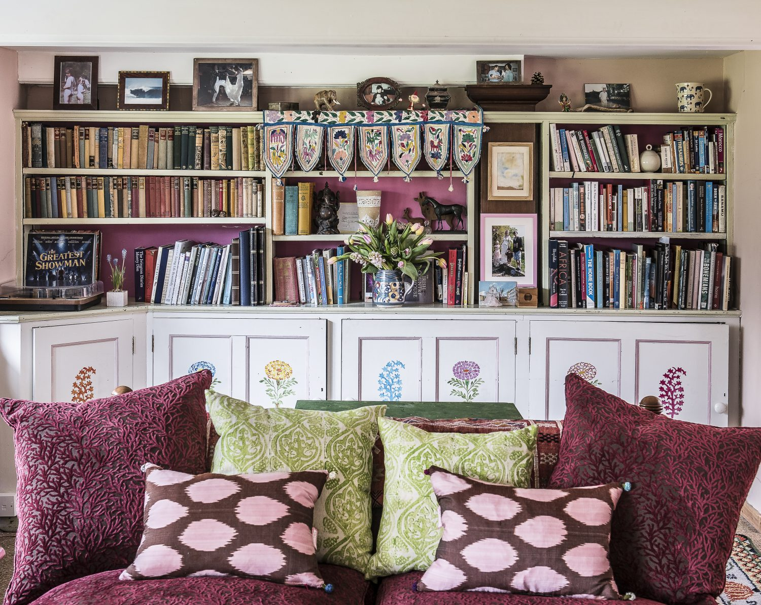 Molly's fabrics on cushions in the sitting room. She painted the flowers on the cupboard doors
