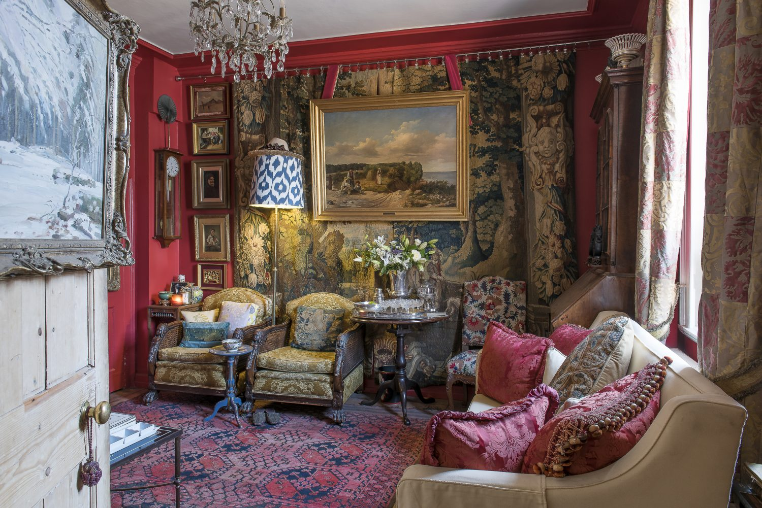 The tapestry on the facing wall of the sitting room is dated to around 1580. Will found the early 20th century Fortuny curtains in an auction. A painting hangs on the back of the door