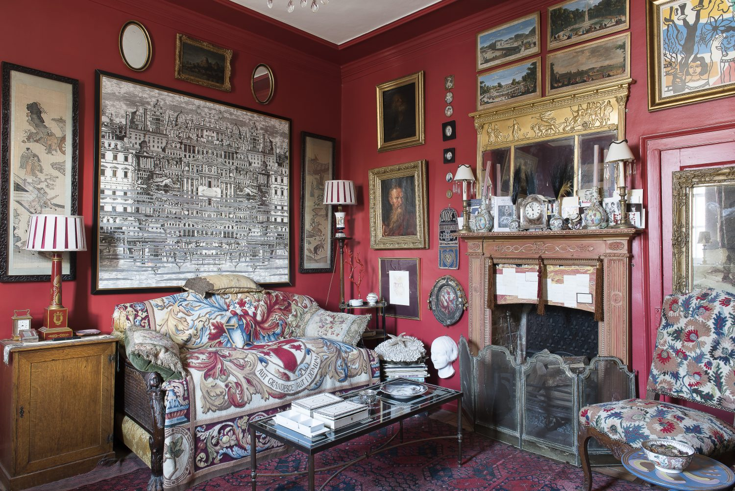 In the drawing room a Fornasetti print hangs over a sofa covered in a 1920s armorial tapestry. The chair is upholstered with a rare 18th century Turkish needlework