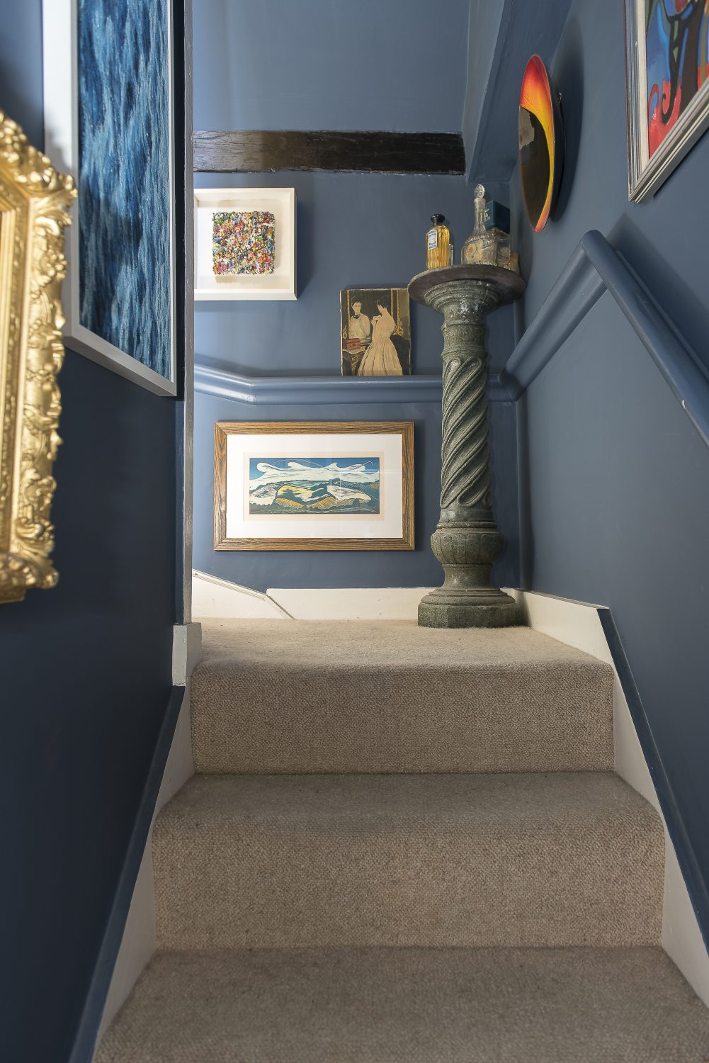 A column on the stairs holds some of Will's large collection of perfumes. The walls are painted in Paynes Grey by Craig & Rose 1829